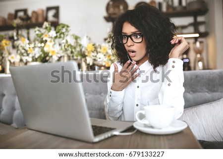 Young girl in glasses surprisingly looking in laptop at cafe. African American girl sitting in restaurant with laptop and cup of coffee on table.Portrait of surprised lady with dark curly hair at cafe #679133227