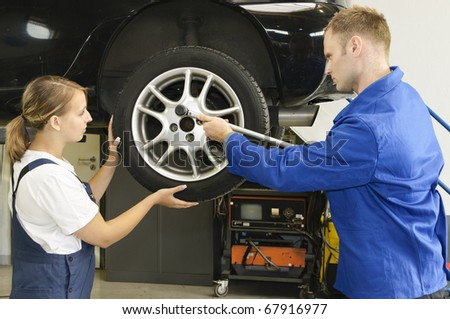 Auto mechanic shows the female trainee changing the wheels of a car in workshop in front of a car #67916977