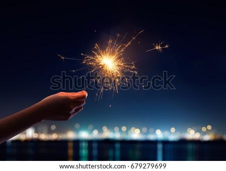 Female hand holding a burning sparkler #679279699