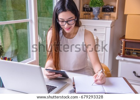 A young business woman using tablet and write it on paper at her modern office, Looking for direction and inspiration. #679293328