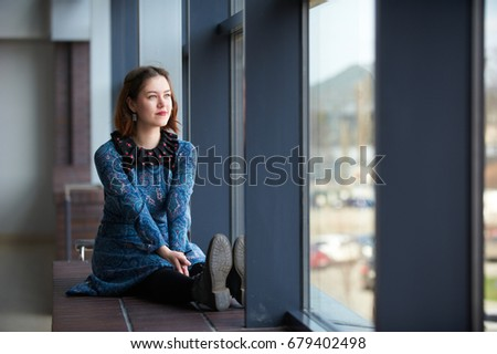 portrait of a young dreamy woman sitting on the window sill #679402498