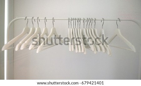 Blank white clothes hangers hang on the bracket #679421401