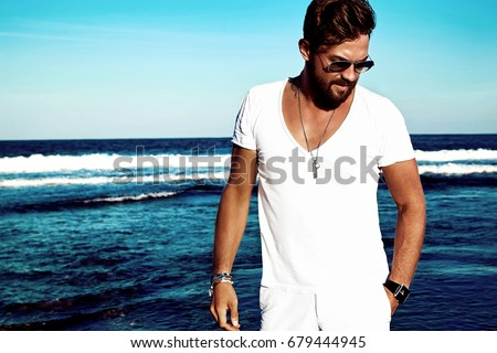 Portrait of handsome fashion man model wearing white clothes posing on blue sea background. In aviator sunglasses #679444945