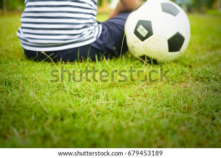 Boy with ball,Or boy with soccer and green grass(focus center of picture) #679453189