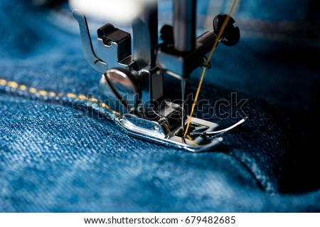 sewing indigo denim jeans with sewing machine, garment industrial concept. Royalty-Free Stock Photo #679482685