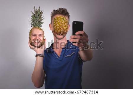 Man swapping face with pineapple on mobile phone