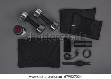 Top view of sportswear, dumbbells and digital devices isolated on grey   Royalty-Free Stock Photo #679527034