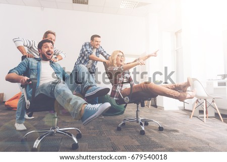 Cheerful colleagues having fun in office chairs #679540018