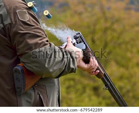 gunman with smoking shotgun after a shot  #679542289