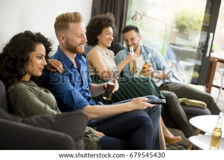 Group of friends watching TV , drinking cider and having fun in the room #679545430