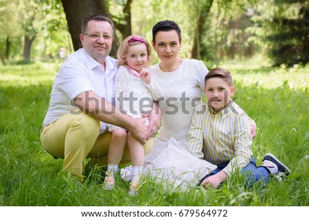 Grandfather with daughter, grandson and granddaughter relax in the park in the summer #679564972