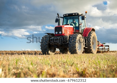 agricultural machinery in the foreground carrying out work in the field #679612312