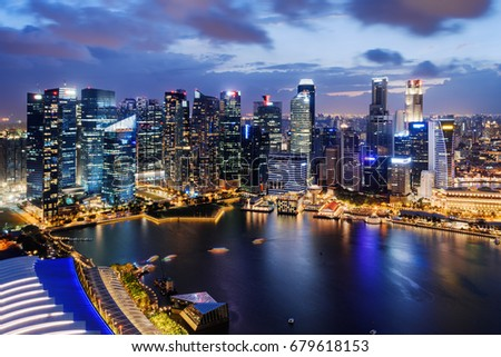 Fantastic night view of skyscrapers at downtown of Singapore. Colorful city lights reflected in water of Marina Bay. Beautiful cityscape. Singapore is a popular tourist destination of Asia. #679618153