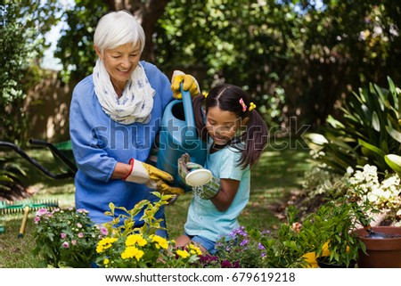 Smiling grandmother and granddaughter watering plants in backyard #679619218