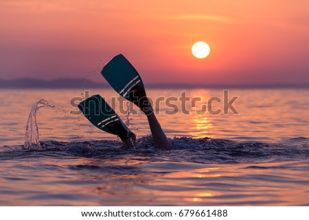 Close up of scuba diver feet with snorkel fins start diving at sunset Royalty-Free Stock Photo #679661488