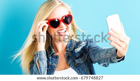 Young woman taking a selfie on a blue background #679748827