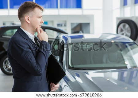 Young professional car dealer holding his clipboard looking away thoughtfully rubbing his chin copyspace decision strategy thinking seller selling profession occupation brainstorming businessman auto #679810906