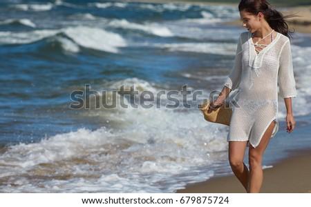 Young woman walking in water wearing white beach  dress #679875724