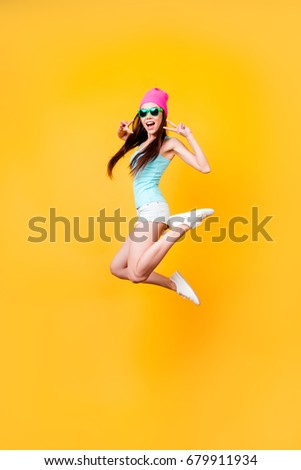 Wow! Happiness, dream, fun, joy concept. Very excited happy cute asian teen is jumping up, wearing casual summer clothes, white shoes, on bright yellow background