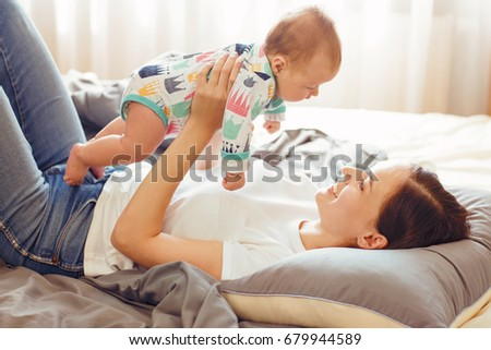 Attractive mother with baby on bed #679944589