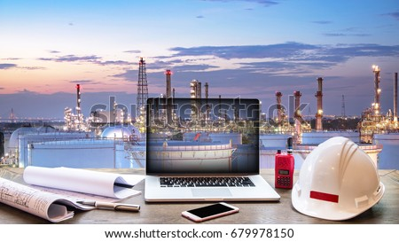Double exposure Engineers holding safety helmet in arms and holding walk talky in hands with oil and gas refinery background on industry concept Royalty-Free Stock Photo #679978150
