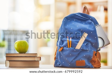 Back to school and happy time! Apple, pile of books and backpack on the desk at the elementary school.  Royalty-Free Stock Photo #679992592