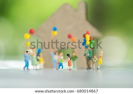 Miniature people, family and children with colorful ballons  standing in front of house. International Day of Families #680014867