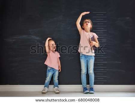 Two children sisters play together. Kid measures the growth on the background of blackboard. Concept of education. Royalty-Free Stock Photo #680048008