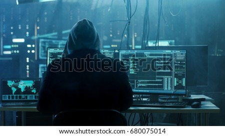 Dangerous Hooded Hacker Breaks into Government Data Servers and Infects Their System with a Virus. His Hideout Place has Dark Atmosphere, Multiple Displays, Cables Everywhere. #680075014
