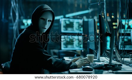 Masked Hacker is Using Computer for Organizing Massive Data Breach Attack on Corporate Servers. They're in Underground Secret Location Surrounded by Displays and Cables. #680078920