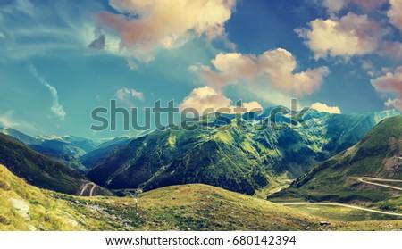 fantastic mountain scenery. colorful clouds in the sky. over the glowing in sunlight mountain peak. with serpentine road. instagram filter. Romania. Carpathians, Ridge Fagarash. Transfagarash road. #680142394