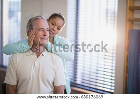 Senior male patient receiving neck massage from female therapist at hospital ward #680176069