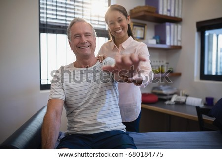 Portrait of smiling female doctor and senior male patient with arms raised at hospital ward #680184775
