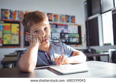 Portrait of boy leaning on desk while studying in classroom #680199043