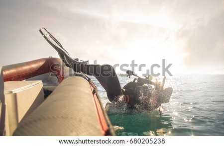 Scuba diver jumping down in the water Royalty-Free Stock Photo #680205238