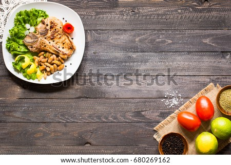 Pork steak homemade cooking with spices leaves lettuce on wooden cutting board, and a dish, on a wooden background, #680269162