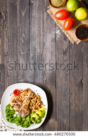Pork steak homemade cooking with spices leaves lettuce on wooden cutting board, and a dish, on a wooden background, #680270500