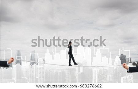 Businessman with blindfolder on eyes walking on rope over cityscape background #680276662