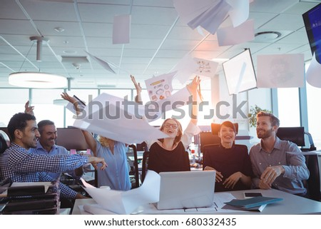 Happy business people tossing papers in air at desk #680332435