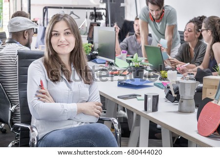 startup office workers team in office working in casual smart woman chief of staff in focus looking at camera hands crossed. young staff discussing project in background. Royalty-Free Stock Photo #680444020