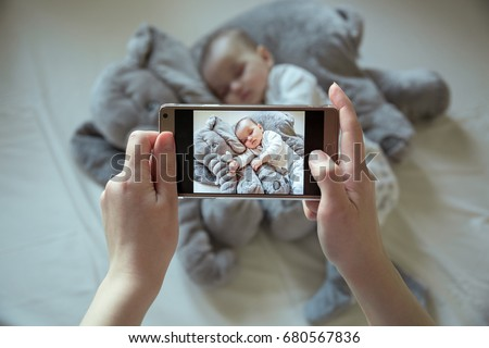 Mother shootin her sleeping newborn baby by smartphone
