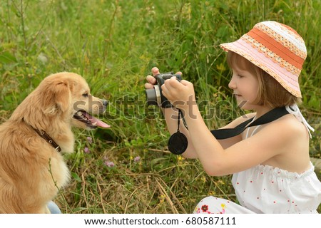 child, kid photographer (a little girl) with a camera taking pictures of the dog