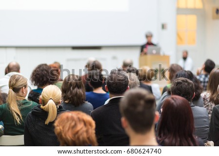 Female speaker giving presentation in lecture hall at university workshop. Audience in conference hall. Rear view of unrecognized participant in audience. Scientific conference event. #680624740