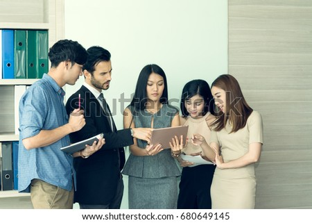 Business people brainstorming during the meeting in conference room. Businessman discussing and pointing to digital tablet during business team looking the screen tablet in meeting room at office. #680649145