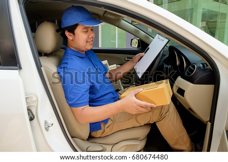 Delivery driver driving with parcels on seat. #680674480