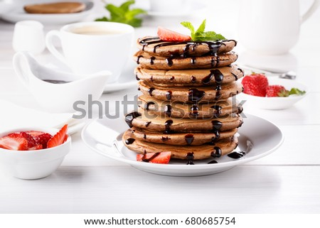 Stack of chocolate pancakes with chocolate topping and strawberries #680685754