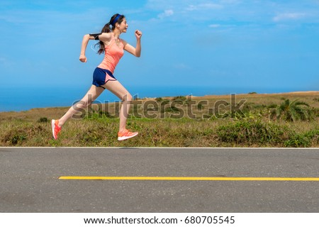 side view photo of professional young female runner player running on road for training personal speed and explosive force at holiday weekend.