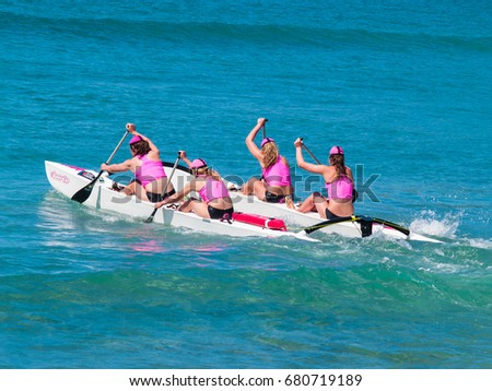 MOUNT MAUNGANUI, NEW ZEALAND - JANUARY 28; Four women in pink tops paddle surf outrigger canoe in competitions at Mount Maunganui, Surf Lifesaving, January 28, 2012, Mount Maunganui, New Zealand #680719189