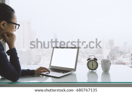 Women freelancer connecting to wireless via laptop computer with coffee mugs and alarm clocks in the morning work room. #680767135