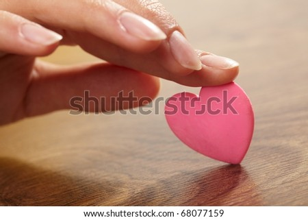 Woman holding pink heart in the hand #68077159